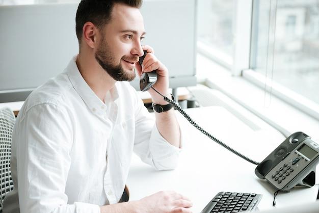 Vue latérale d'un homme parlant au téléphone