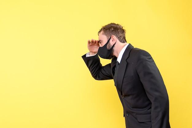 Vue latérale d'un homme pensant avec costume et cravate mettant sa main sur son front avec du jaune
