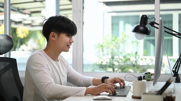 Vue latérale de l'homme pigiste en tenue décontractée assis au bureau à domicile et travaillant sur un projet avec ordinateur