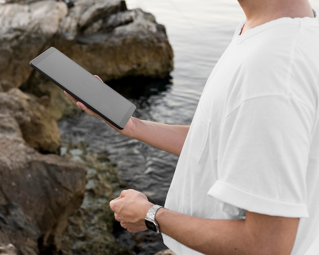 Vue latérale de l'homme à la plage tenant la tablette