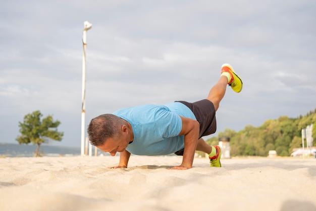 Vue latérale d'un homme plus âgé travaillant sur la plage