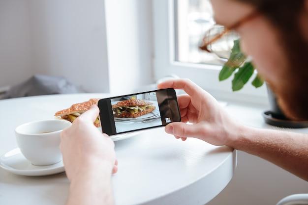 Vue latérale d'un homme prenant une photo de sa nourriture au café