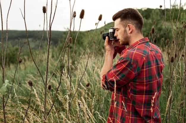 Vue latérale homme prenant des photos