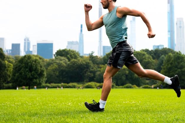 Vue latérale d'un homme qui court sur l'herbe