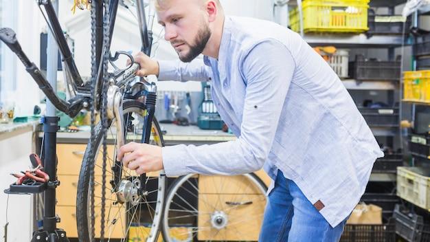 Vue latérale d'un homme réparant un vélo