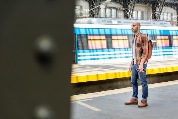 Vue latérale homme avec sac à dos voyageant