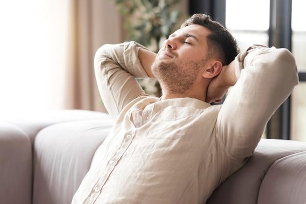 Vue latérale homme se détendre sur le canapé