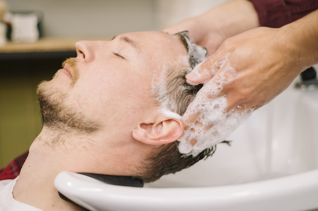 Vue latérale de l'homme se laver les cheveux au salon de coiffure