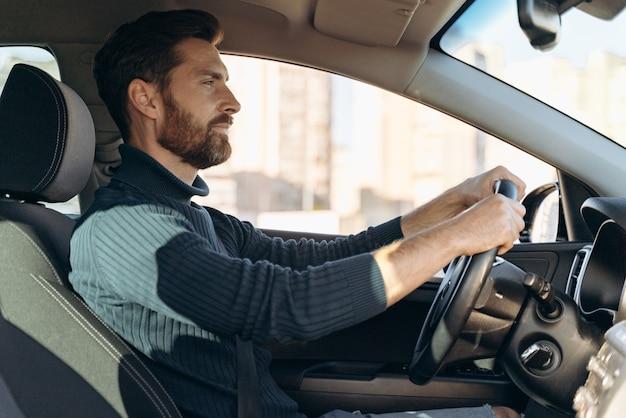 Vue latérale de l'homme sérieux et confiant conduisant à la voiture et se sentant confiant tout en regardant la route pendant la conduite. stock photo