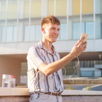 Vue latérale d'un homme souriant ayant un appel vidéo à l'extérieur