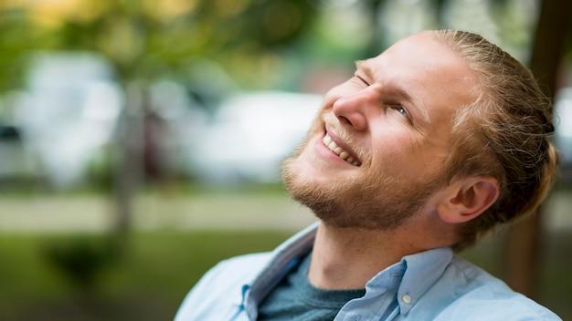 Vue latérale de l'homme souriant à l'extérieur avec espace copie