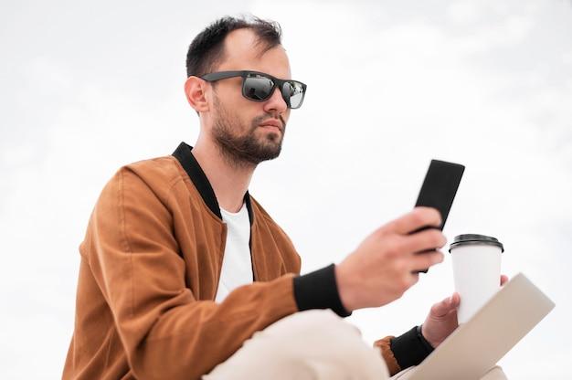 Vue latérale de l'homme travaillant à l'extérieur sur un ordinateur portable tout en buvant un café