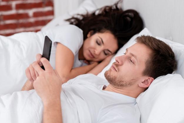 Vue latérale homme vérifiant son téléphone à côté de la petite amie endormie