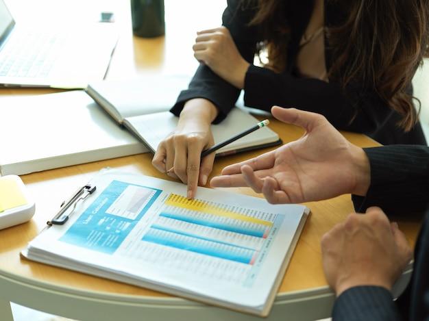 Vue latérale des hommes d'affaires remet la paperasse commerciale tout en consultant sur leur projet