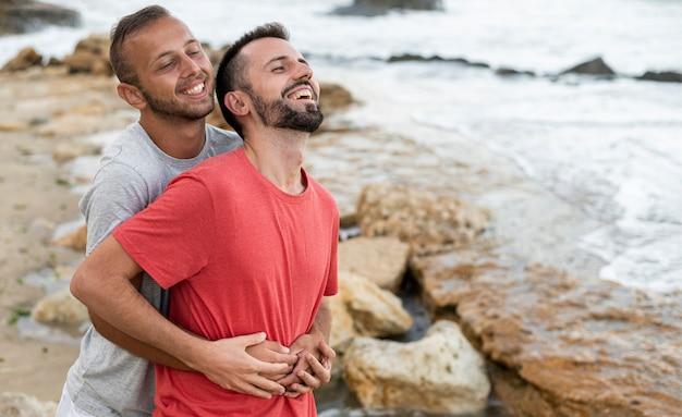 Vue latérale des hommes heureux au bord de la mer