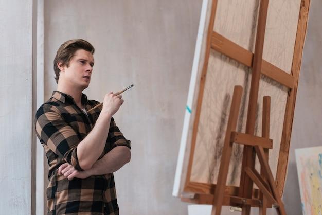 Vue latérale jeune artiste regardant sa photo