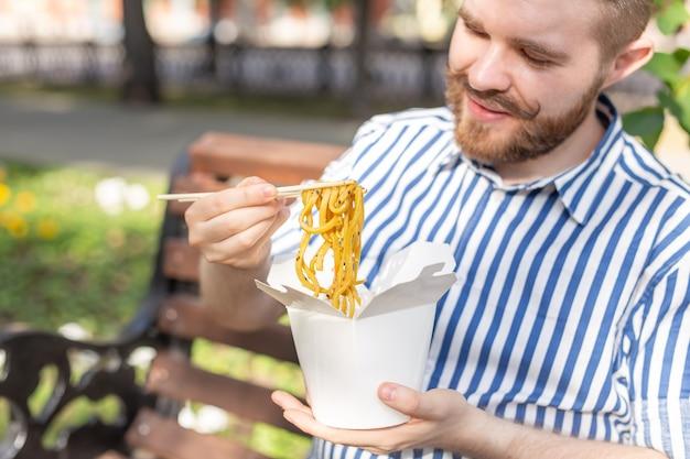 Vue latérale d'un jeune beau mec hipster mangeant des nouilles chinoises dans une boîte à lunch alors qu'il était assis dans un banc de parc par une journée d'été ensoleillée.