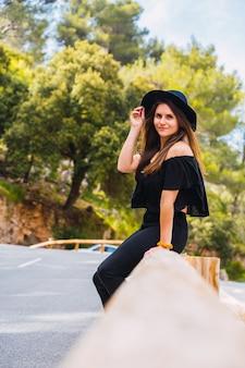 Vue latérale d'une jeune brune en tenue tendance touchant un chapeau et regardant ailleurs alors qu'elle était assise sur une barrière contre des arbres luxuriants dans un parc