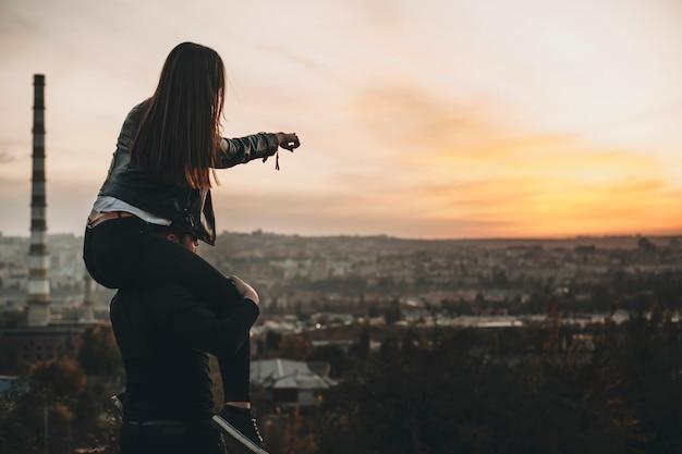 Vue latérale d'une jeune femme anonyme assise sur les épaules de son petit ami et pointant vers un coucher de soleil incroyable sur la ville moderne