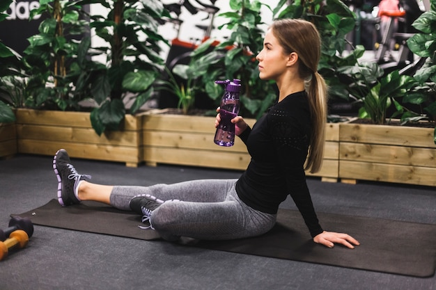 Vue latérale d'une jeune femme assise sur un tapis d'exercice avec une bouteille d'eau