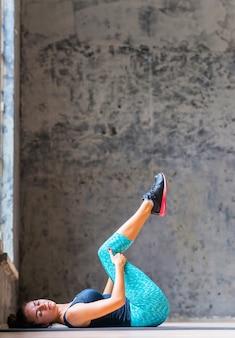 Vue latérale d'une jeune femme athlétique, faire du yoga sur tapis d'exercice