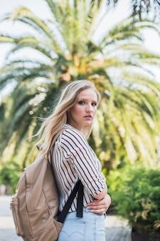 Vue latérale d'une jeune femme blonde avec son sac à dos