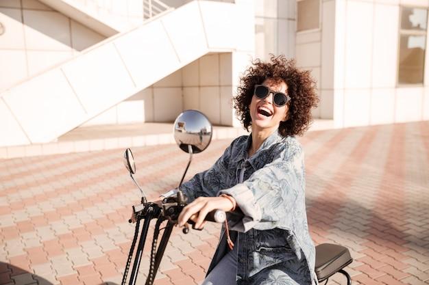 Vue latérale d'une jeune femme bouclée joyeuse en posant des lunettes de soleil