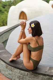 Vue latérale d'une jeune femme brune bronzée moderne se relaxant dans une piscine extérieure
