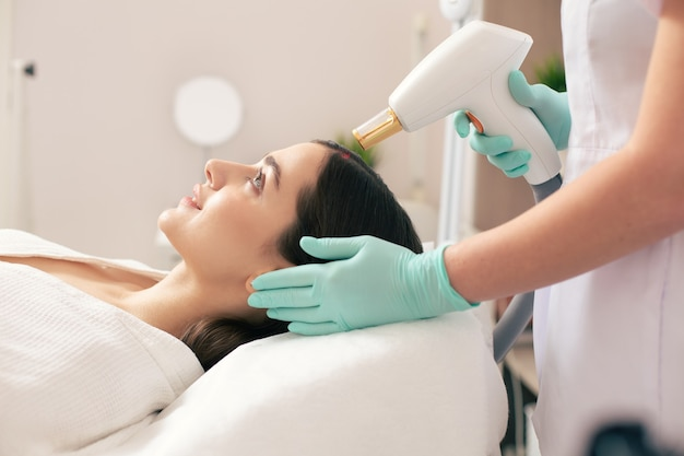 Vue latérale de la jeune femme calme allongée et subissant la procédure d'élimination des cicatrices au laser