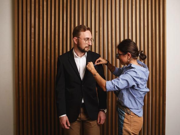Vue latérale d'une jeune femme élégante ajustant la veste d'un homme mignon dans un intérieur d'appartement moderne.