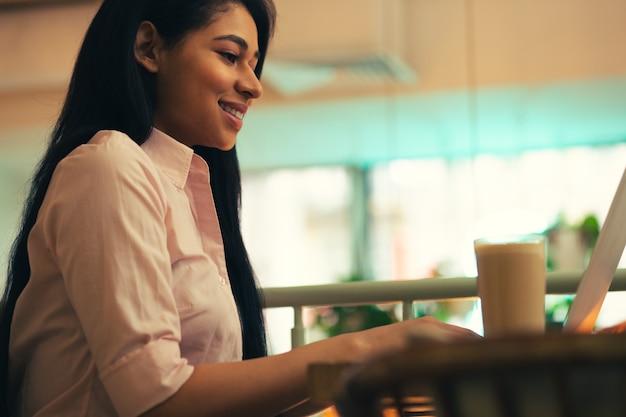 Vue latérale d'une jeune femme joyeuse assise à la table avec un verre de café à ses côtés et souriant