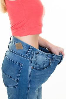 Vue latérale jeune femme méconnaissable en pantalon oversize après un régime en studio shot