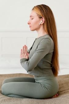 Vue latérale jeune femme méditant à la maison