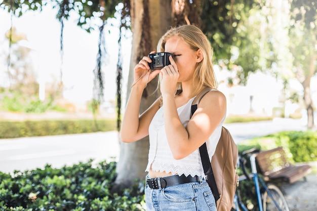 Vue latérale de la jeune femme, prendre des photos en plein air