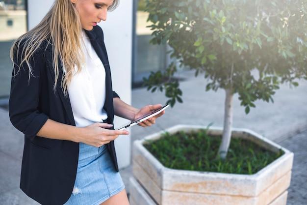 Vue latérale de la jeune femme regardant la tablette numérique