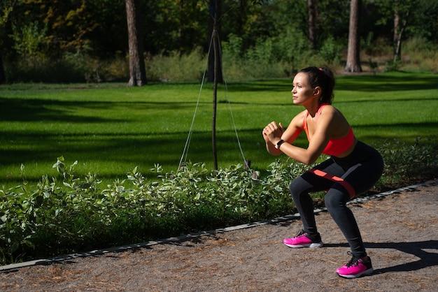 Vue latérale d'une jeune femme sportive exerçant et faisant des squats debout sur un chemin de roulement dans le parc urbain. concept de formation en plein air.