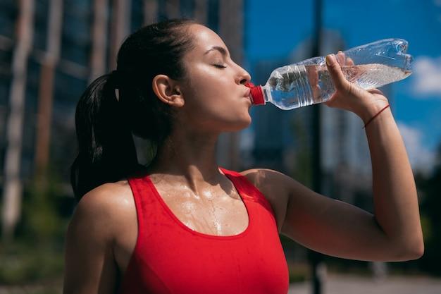 Vue latérale d'une jeune femme en sueur athlétique avec queue de cheval ondulée brune portant un soutien-gorge de sport rouge et de l'eau potable à partir d'une bouteille en plastique