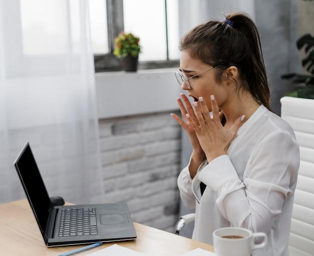 Vue latérale jeune femme travaillant à domicile