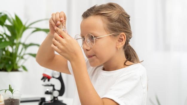 Vue latérale d'une jeune fille apprenant la science au microscope