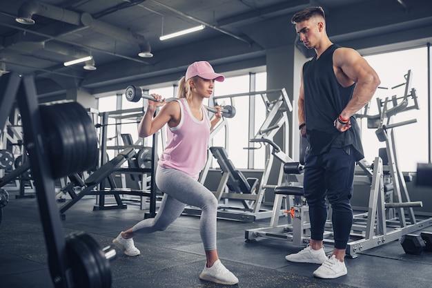Vue latérale d'une jeune fille blonde sportive concentrée et motivée en tenue de sport faisant des exercices de jambes tout en étant un entraîneur personnel musclé beau la surveillant dans la salle de sport