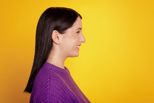 Vue latérale d'une jeune fille joyeuse, un sourire positif et heureux, un espace vide isolé sur un fond de couleur jaune
