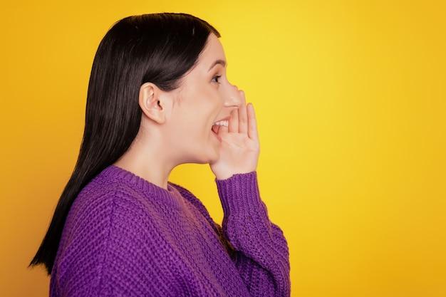 Vue latérale d'une jeune fille joyeuse, sourire positif et heureux, regardez l'espace vide, dites raconter des nouvelles isolées sur fond de couleur jaune