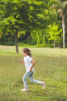 Vue latérale d'une jeune fille qui court au parc