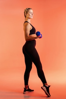 Vue latérale jeune formation féminine avec des poids