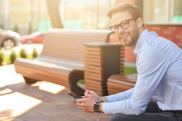 Vue latérale d'un jeune homme d'affaires heureux tenant un smartphone regardant la caméra et souriant tout en