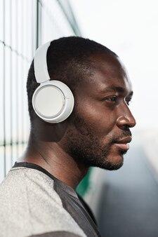 Vue latérale d'un jeune homme africain dans des écouteurs sans fil écoutant de la musique tout en se tenant à l'extérieur
