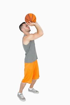 Vue latérale d'un jeune homme lançant un ballon de basket
