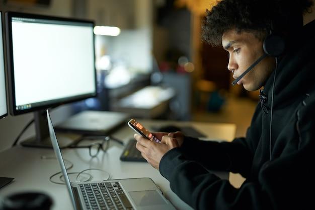 Vue latérale d'un jeune homme portant un casque assis à la table devant des écrans d'ordinateur et
