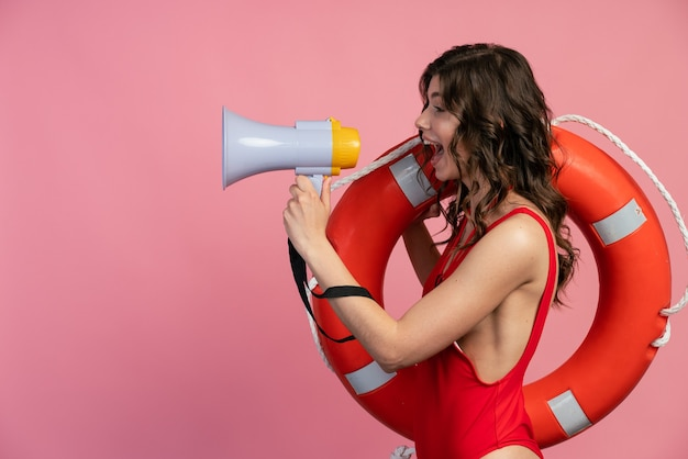 Vue latérale d'un jeune sauveteur séduisant sur fond rose parlant dans un haut-parleur. fille en maillot de bain avec une bouée de sauvetage sur son épaule.