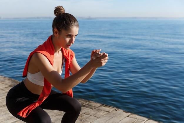 Vue latérale d'une jeune sportive concentrée faisant des squats près de la mer, s'entraînant au bord de la mer.